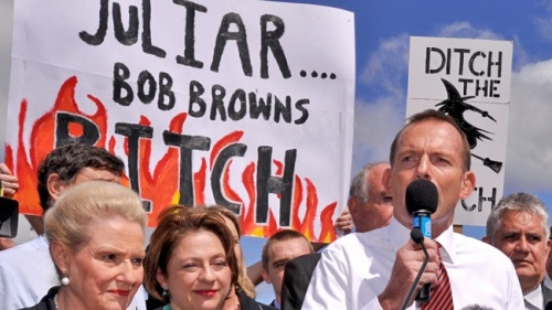 Australia's current Prime Minister Tony speaking behind misogynist placards about the then PM Julia Gillard